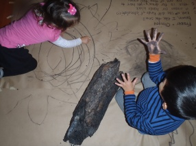 Ohnyou and Frazer draw with charred pieces of a tree Barry brought in to show us.