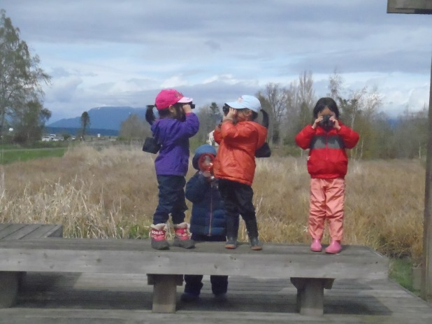 Kate's small Owls group using binoculars and magnifying glasses.